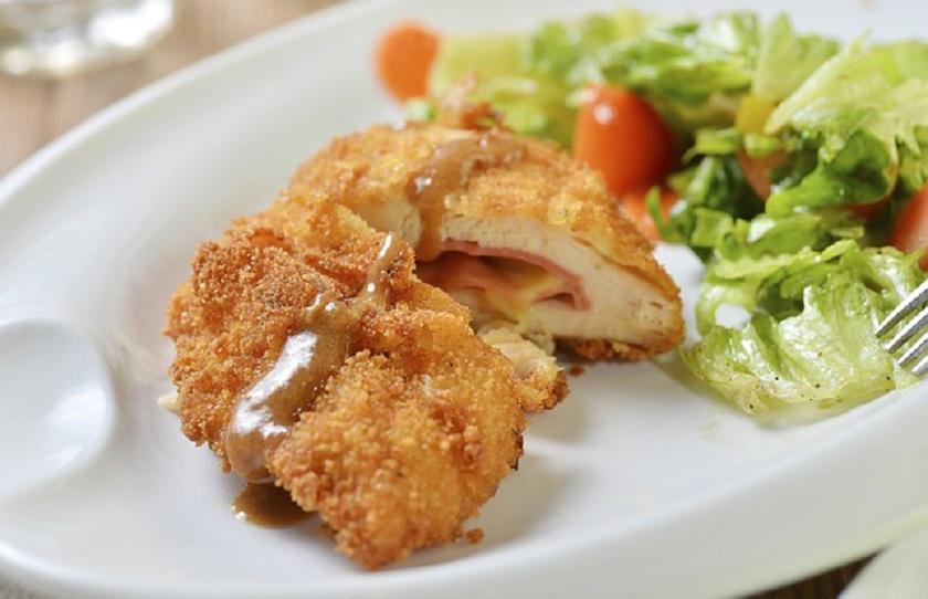 Отбивная в темной панировке: ароматное мясо с салатом и соусом